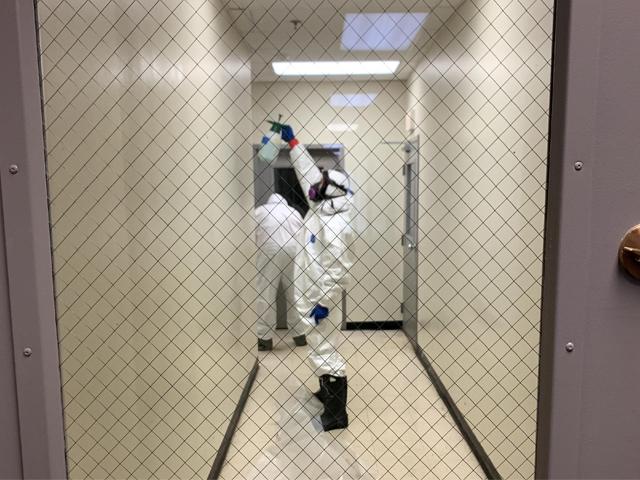 Far spraying disinfectant in hallway